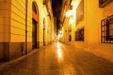 Fototapeta Uliczki - Narrow street at night in the old town in Valencia, Spain