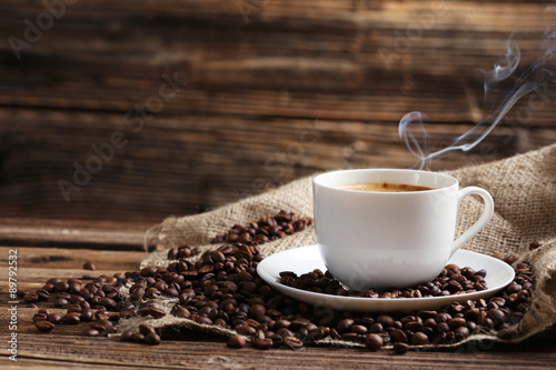 Spoed Foto op Canvas Cafe Cup of coffee with coffee beans on a brown wooden background