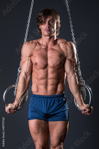 Tuinposter Gymnastiek Strong gymnast guy on the rings