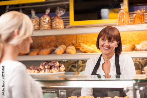 Staande foto Bakkerij Cheerful saleswoman is serving a customer in bakery