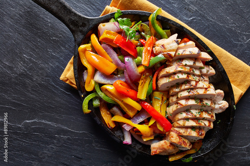 Stampe  mexican grilled chicken fajitas in iron skillet shot from overhead on slate
