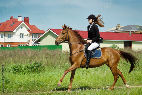 Poster Ouest sauvage Beautiful girl jockey ridding horse in a field