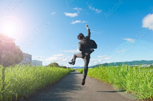 Fotografija  道路でジャンプをするスーツのビジネスマン