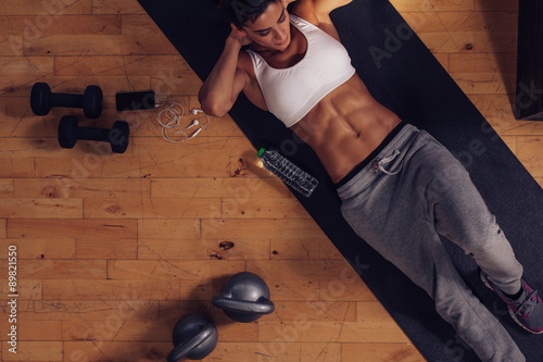 Fotografiet  Muscular woman doing abs workout in gym