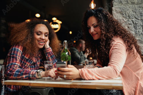 Fototapeta Young women sitting at a cafe using mobile phone obraz na płótnie