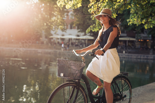 Fotografie, Obraz  Attractive young woman riding bicycle along a pond in city park