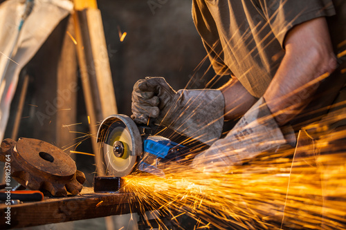 Photo  Close-up of worker cutting metal with grinder
