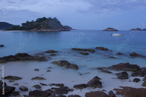 Photographie  Long exposure flat sea view with rocks in foreground at dusk