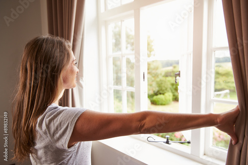 Fotografie, Obraz  Woman Standing By Bedroom Window And Opening Curtains