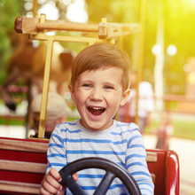 Boy Driving A Car On Merry-go-round