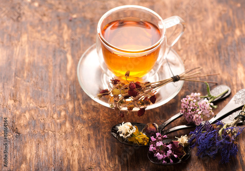 Cup of herbal tea with wild flowers and various herbs Wallpaper Mural