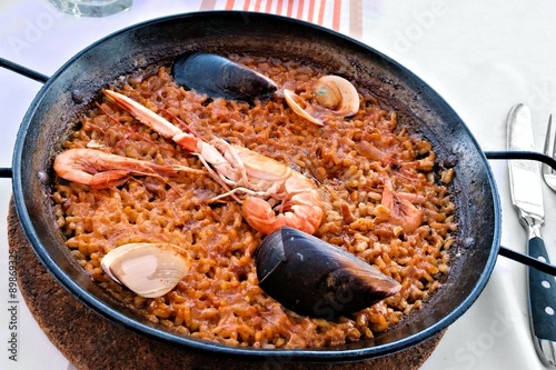 Photo  Traditional Spanish seafood paella in rustic pan on white table background