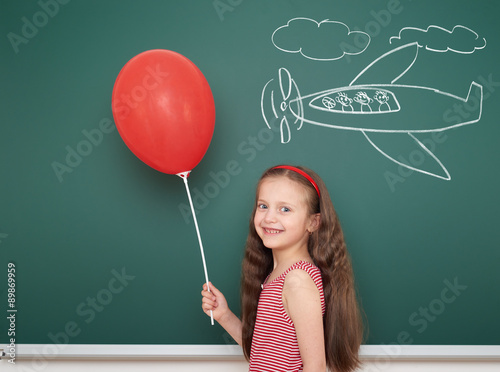 Photo  girl with balloon drawing plane on school board