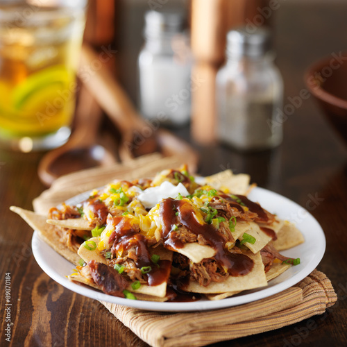 Cuadros en Lienzo barbecue pulled pork nachos with sourcream, green onions and melted cheese