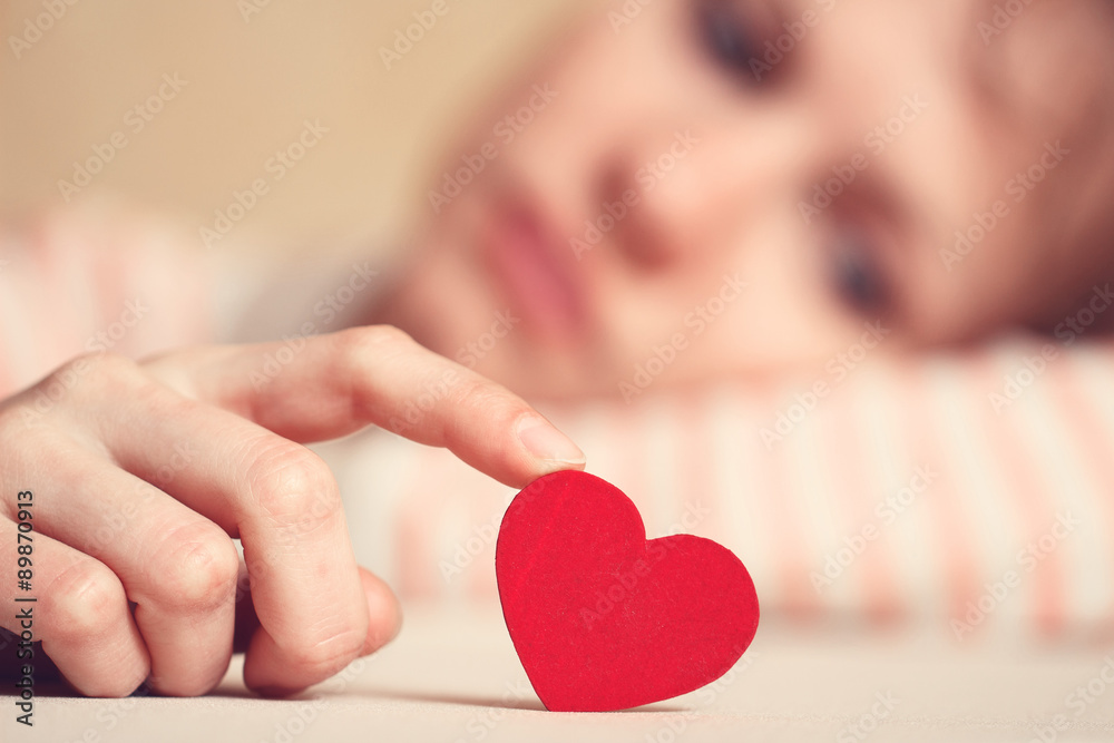 Fototapeta Sad and upset girl is touching heart symbol with finger