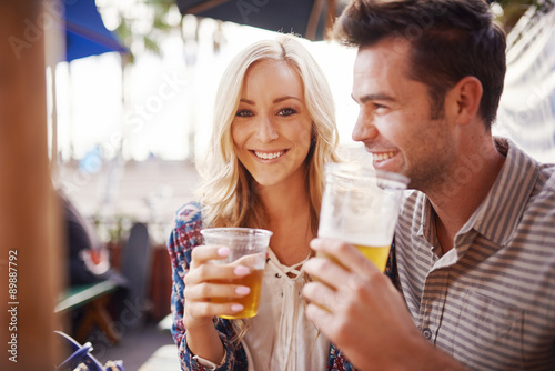 Foto romantic couple drinking beer together in outdoor beach side pub or bar