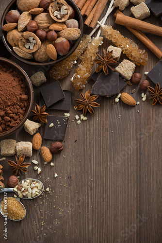 Foto op Plexiglas Chocolade chocolate, cocoa, nuts and spices on wooden background top view