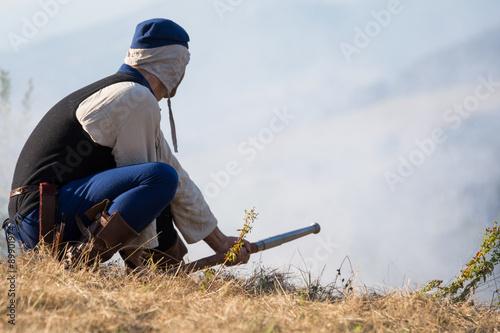 Fotografía  Mann mit alter Schusswaffe in adäquater Kleidung