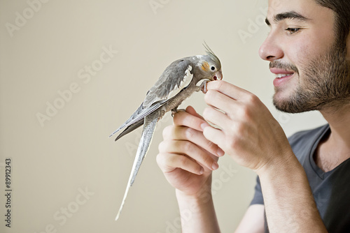 Valokuva  Attractive man playing with his parrot indoors