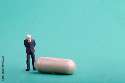 Fotografia  manager dell' industria farmaceutica in miniatura con pillola