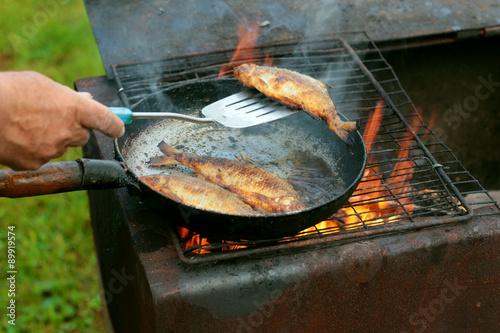 Fényképezés fish frying in oil on the fire