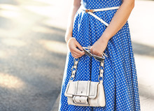 Fashionable Woman With White Bag In Her Hands And Blue Dress