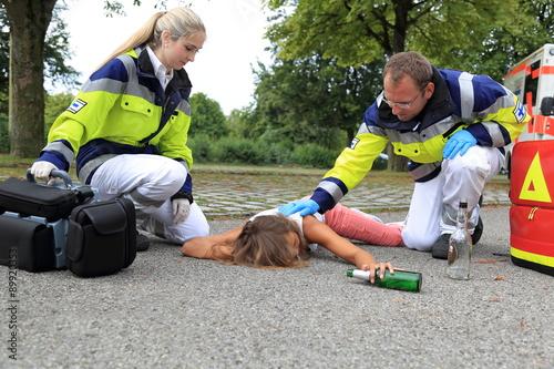 Fényképezés  Junge Frau betrunken am Boden mit Sanitäter