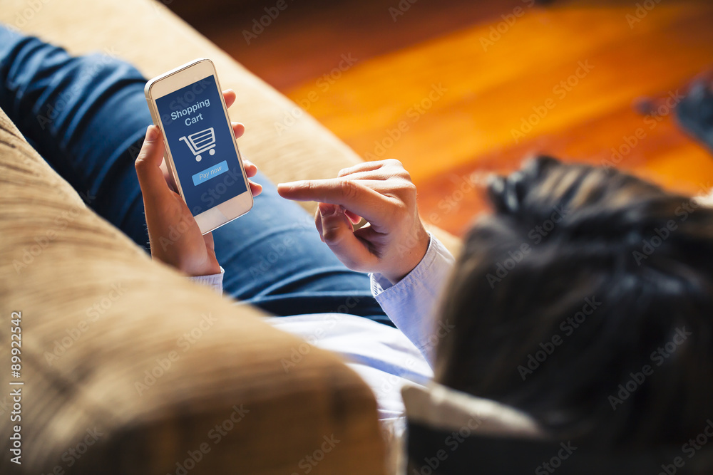 Fototapety, obrazy: Woman shopping by mobile phone laying at home. Blue screen. She is laying on the sofa.