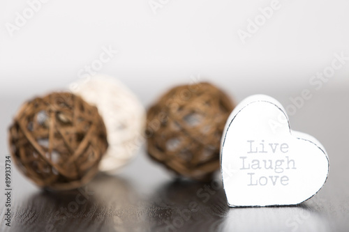Photo  Three wicker balls with a white heart contain the text live laugh and love