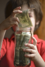 Child Entering Their Savings In A Jar