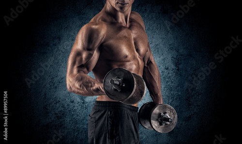 Spoed Foto op Canvas Fitness Muscular man with dumbbells on black background