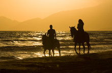 Horse Rider Couple At Sunset Beach, Next To The Sea