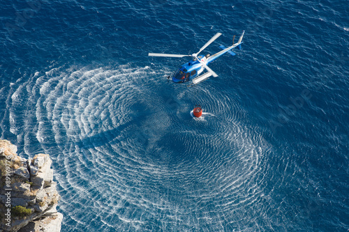 Tuinposter Helicopter Fire fighter helicopter collect water over the sea