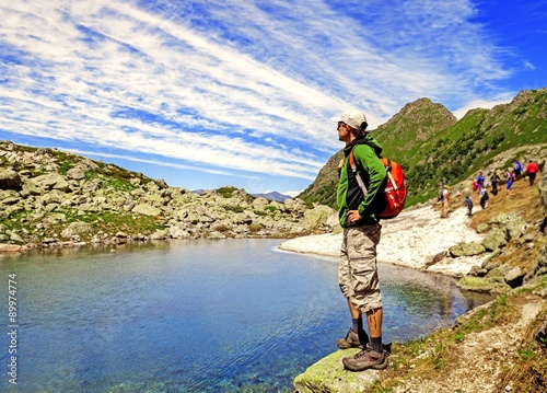 Man hiking in the mountains on a tourist track near a lake