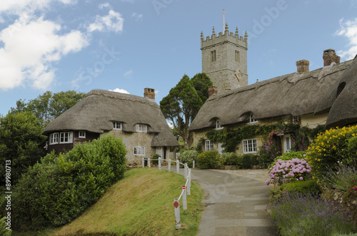 Fotografia The pretty thatched cottages of Church Hill, with All Saints church in the background