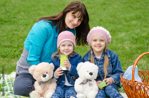 Valokuva  Mum embraces daughters on a picnic