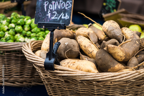 Fotografie, Obraz  Whicker basket filled with sweet potatoes and a sign