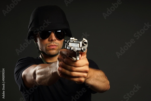 Special ops officer SWAT in black uniform on gray background