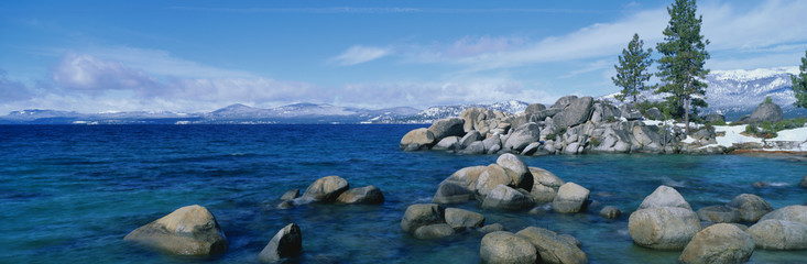 This is Lake Tahoe after a winter snow storm. There is a full moon over the lake and snow on the sandy shore.