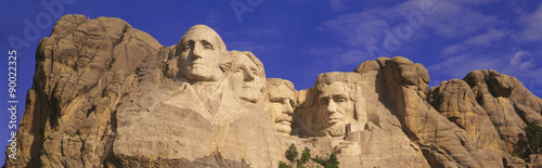 Recess Fitting Historic monument This is a close up view of Mount Rushmore National Monument against a blue sky. It shows the four faces of George Washington, Thomas Jefferson, Theodore Roosevelt, and Abraham Lincoln.