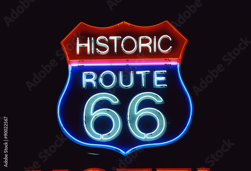 In de dag Route 66 This is a road sign that says Historic Route 66. It is a neon sign in red, white and blue against a black night sky.
