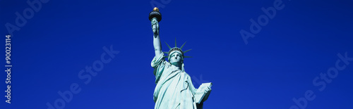 This is the top half of the Statue of Liberty against a blue sky in horizontal format Wallpaper Mural