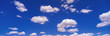 canvas print picture - This is an image of a blue sky with white puffy clouds scattered throughout.