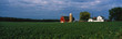 canvas print picture - This is a farm with a silo and barn. Directly behind it sits a white farmhouse. It sits in the middle of a green farm field.