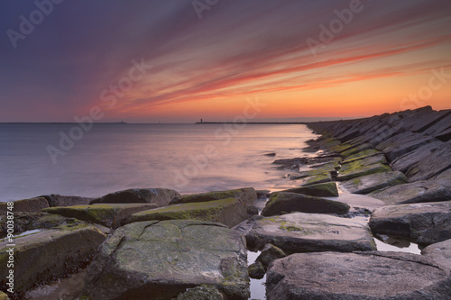 Fototapeta Sunset over harbour entrance at sea in IJmuiden, The Netherlands