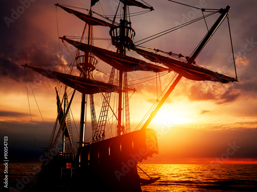 Fotografering  Old ancient pirate ship on peaceful ocean at sunset.