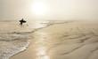 Man with surfboard on the beautiful foggy beach.