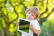 Smiling happy little child holding tablet pc, outdoors