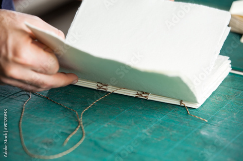 Fotografia, Obraz  Hand Manufacturing Book On Table
