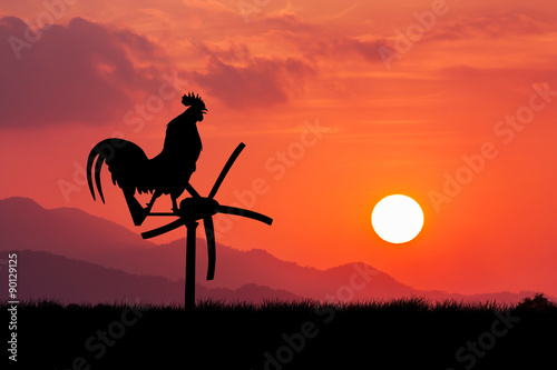 Poster Corail Roosters crow stand on a wind turbine. In the morning sunrise ba